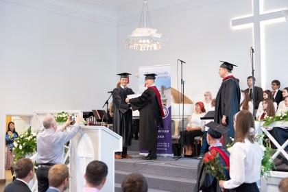 Алексей Мюллер получает диплом бакалавра из рук председателя попечительского совета МБС Виктора Крутько